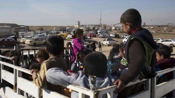 Children wait on the back of a pick-up truck outside the Khazer checkpoint on the road to Mosul (Bram Janssen/AP)