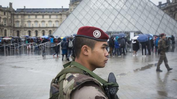 A soldier patrols the courtyard of the Louvre (AP)