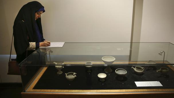 An Iranian journalist takes notes as she covers a show displaying some 550 ancient Persian artworks returned by Western countries (Vahid Salemi/AP)