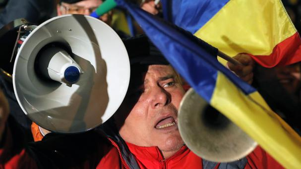 A man shouts during a pro-government protest in Bucharest, Romania (Vadim Ghirda/AP)