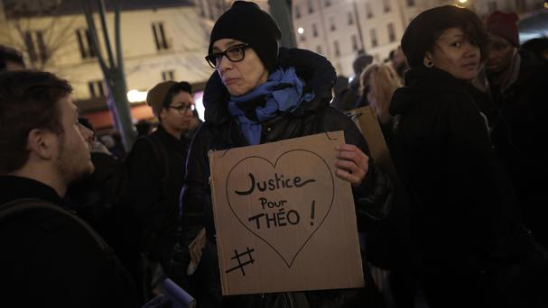 A demonstrator holds a poster during a protest against police violence in Paris (AP)