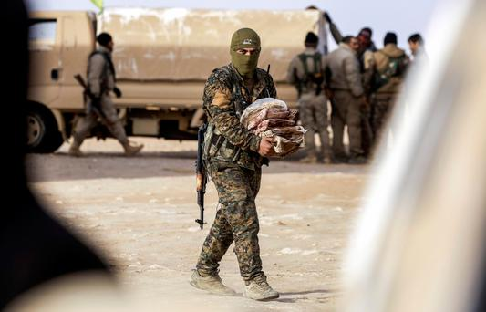 A member of the Syrian Democratic Forces (SDF) carries supplies near the village of Bir Fawaz during their offensive against Isil. Photo: Delil Souleman/Getty Images