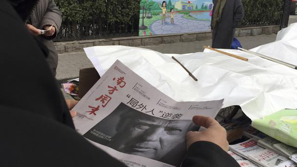A Chinese newspaper at a news-stand in Beijing carries a photo of Donald Trump with the headline 'Outsider counter attack' (AP)