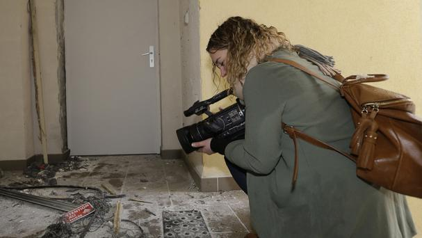 A video-journalist films the wreckage of an entrance of an apartment building after a raid of a French anti-terrorist police unit in Clapiers, southern France (AP)