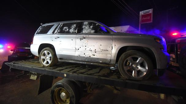 A bullet-ridden sports utility vehicle is taken away by authorities after a gun battle with Mexican marines in Tepic, Nayarit state (Chris Arias/AP)