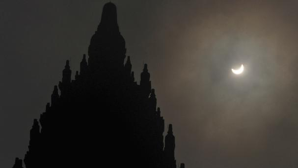 A partial solar eclipse is seen behind the 9th-century Prambanan Temple in Yogyakarta, Indonesia (AP)