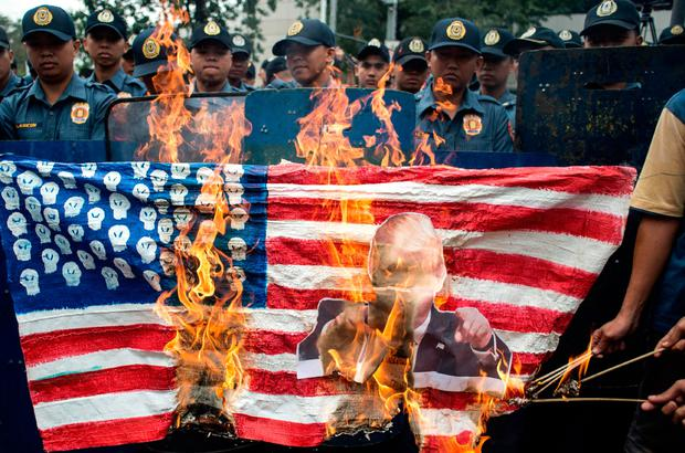 Activists burn a US flag and an image of President Donald Trump during a protest in front of the US embassy in Manila, Philippines. Photo: Noel Celis/Getty