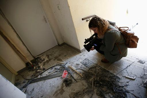 A journalist films the debris of an explosion in front of an apartment building after a raid by French police in Clapiers, near Montpellier, southern France, yesterday. Photo: Jean-Paul Pelissier