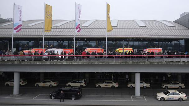 Travellers wait outside Hamburg Airport (Axel Heimken/dpa via AP)