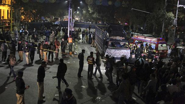 Police and security officers cordon off the area of a deadly bombing in Lahore, Pakistan (KM Chaudhry/AP)