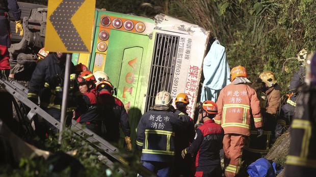 Members of a rescue team at the scene where a bus collided with a car on a road in Taipei, Taiwan (AP)