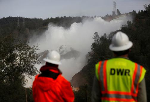 Staff with the California Department of Water Resources watch as water is released from the Lake Oroville Dam. Photo: Getty