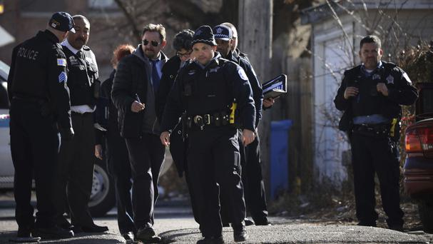 Chicago police investigate the scene of a fatal shooting in which a toddler and a man aged 26 died (Chicago Tribune via AP)