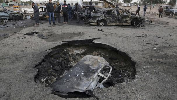 The bomb in the south-western al-Bayaa neighbourhood blew a huge crater in the road (AP)