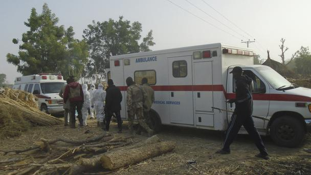 Emergency workers and security forces at the site of a suicide bomb attack on the outskirts of Maiduguri (AP)
