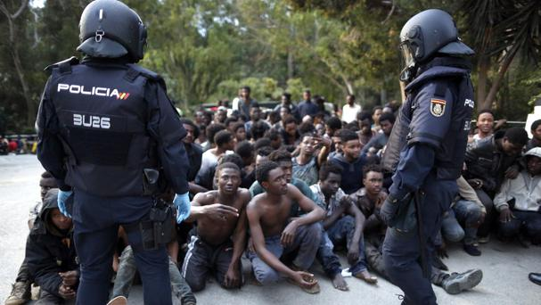 Migrants are watched by Spanish police after storming a fence to enter the enclave of Ceuta (AP)
