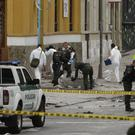 Police and investigators inspect the site where a home-made bomb exploded near the Santamaria bull ring in Bogota (AP)