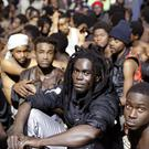 Migrants sit on the ground after storming a fence to enter the Spanish enclave of Ceuta (AP/Jesus Moron)