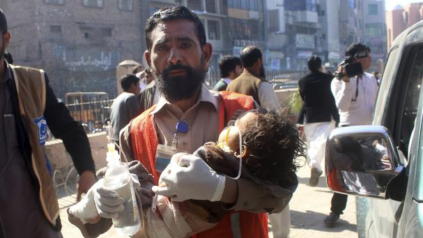 A rescue worker carries an injured child to hospital in Peshawar (AP)