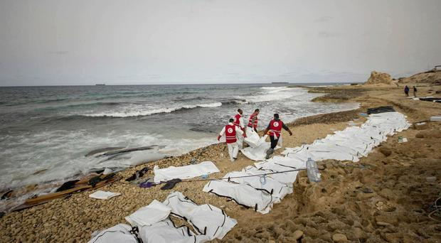 Libyan Red Crescent workers recover bodies of people that washed ashore, near Zawiya, Libya. It says that more bodies may yet surface. Photo: Mohannad Karima/AP
