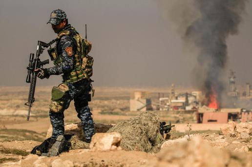 Smoke rises from sugar factory as Iraqi security forces sniper aims his weapon toward Mosul's airport during a battle with islamic state's militants south west Mosul