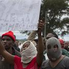 South Africans wave anti-immigration placards during a protest in Pretoria (AP/Yeshiel Panchia)