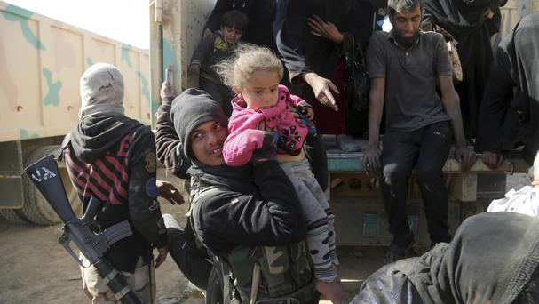 Iraqi Army soldiers help civilians as they flee due to fighting between Iraqi forces and Islamic State in Mosul (AP/Khalid Mohammed)