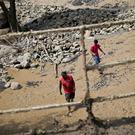 Men walk through sludge brought by the overlowing of Estero San Jose River in San Alfonso, Santiago. (AP/Esteban Felix)