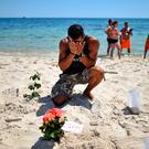 A man prays after laying flowers on Marhaba beach where 38 people were killed on Friday in a terrorist attack in Souuse, Tunisia