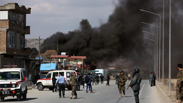 Smoke rises from a district police headquarters after a suicide bombing in Kabul (AP)