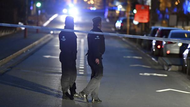Police officers stand at a cordon during the investigation of a suspect car in the centre of Brussels (Geert Vanden Wijngaert/AP)
