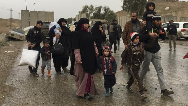Civilians flee their homes on the western side of Mosul (Mohammed Numan/AP)