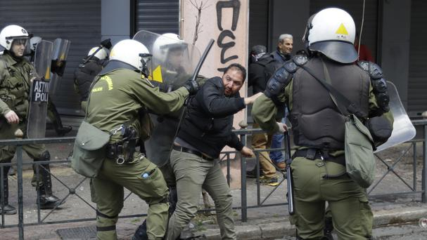 A protesting farmer tries to escape from riot police officers during clashes outside the greek Agriculture Ministry. (AP/Thanassis Stavrakis)