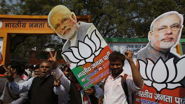Bharatiya Janata Party supporters raise cutouts of Indian Prime Minister Narendra Modi as they celebrate winning seats in the state of Uttar Pradesh (AP Photo/Rajesh Kumar Singh)