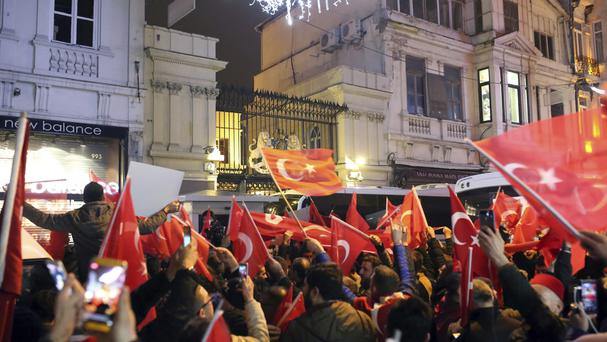 Supporters of Turkey's President Recep Tayyip Erdogan wave flags outside the Dutch consulate in Istanbul (AP)