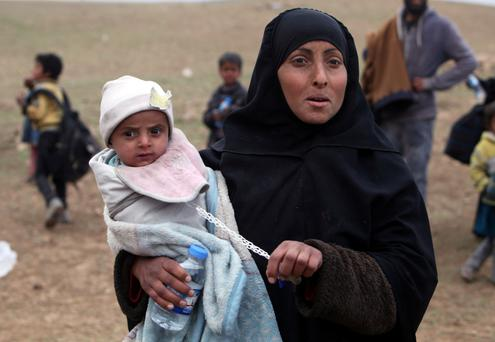An Iraqi displaced woman who fled her home carries her child in the village of Badush, northwest of Mosul. Photo: Reuters