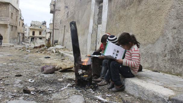 Children review manuals distributed by Unicef-supported volunteers on the risks of unexploded remnants of war, in east Aleppo, Syria (Khudr Al-Issa/Unicef via AP)