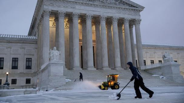 Workmen clear snow in front of the Supreme Court on Capitol Hill in Washington (J Scott Applewhite/AP)