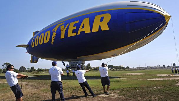 This 2015 photo shows ground crew mooring the Goodyear Blimp Spirit of Innovation in Carson, California (Richard Vogel/AP)