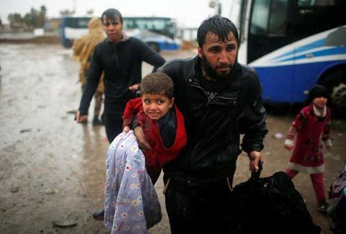Displaced Iraqis flee their homes in the rain in western Mosul. Photo: Reuters