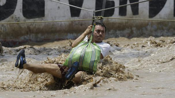 A man is pulled to safety in a zipline harness in Lima (AP Photo/Martin Mejia)