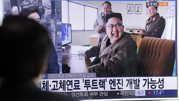 A man in Seoul watches a TV news programme showing an image of North Korean leader Kim Jong Un at the rocket test site (Ahn Young-joon/AP)