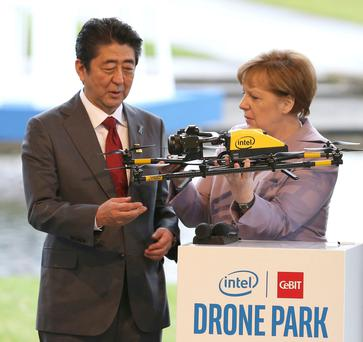 German Chancellor Angela Merkel and Japanese Prime Minister Shinzo Abe, left, look at a drone on the Intel stand during their tour of the CeBIT trade fair in Hanover, Germany, yesterday. Photo: Friso Gentsch/dpa via AP