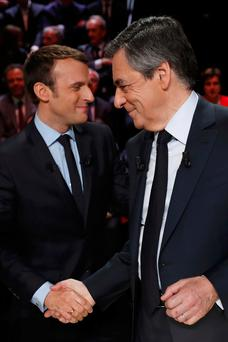 Emmanuel Macron and François Fillon shake hands before the debate last night. Photo: Patrick Kovarik/Reuters