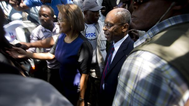 Jean-Bertrand Aristide, centre right, walks with former presidential candidate Maryse Narcisse in Port-au-Prince, Haiti, on the day of the motorcade shooting (AP)