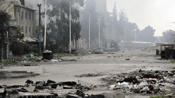 Damaged streets after clashes erupted between Syrian government forces and rebels in Damascus (Sana/AP)