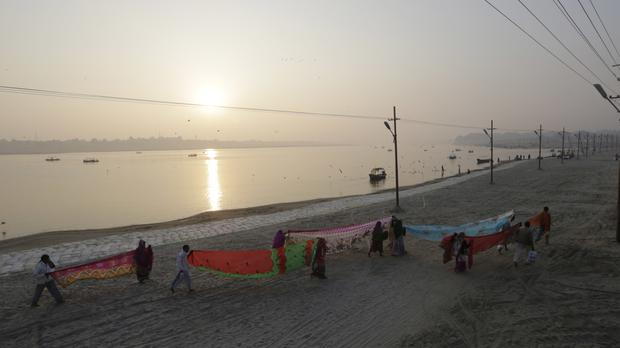 Hindu devotees dry their clothes after taking a dip at Sangam, the confluence of the rivers Ganges, Yamuna, and Saraswati (AP)