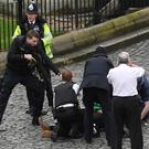 A policeman points his gun at the suspected attacker downed outside the Palace of Westminster