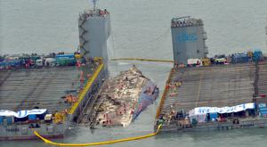 Workers prepare to lift the sunken Sewol ferry, centre, off Jindo, South Korea. Photo: Park Gyung-woo/Hankookilbo via AP