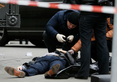 Investigators inspect the body of Denis Voronenkov, who was shot dead in Kiev yesterday. Photo: Reuters